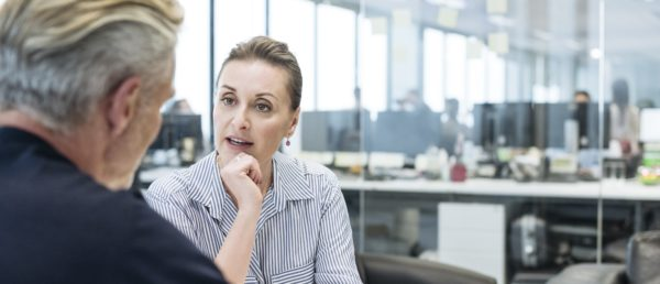 Mid adult woman and mature man in business meeting, two business people in office using tablet